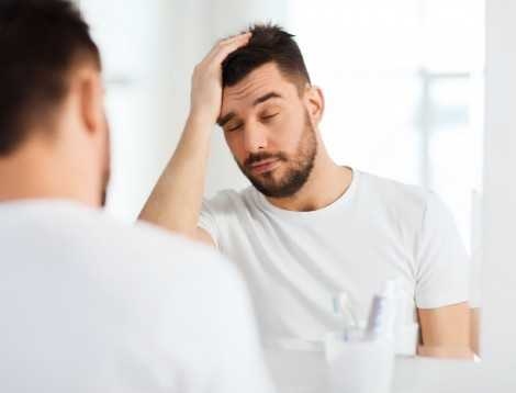 sleepy young man in front of mirror at bathroom