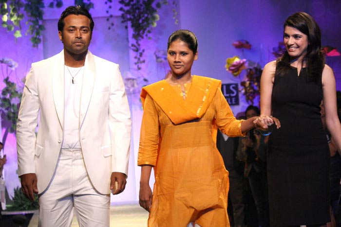 Leander Paes walks with a girl who was rescued from a red light area
